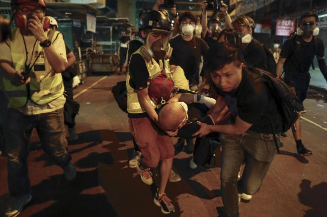 Medical staff and protesters carry an injured during protests in Hong Kong
