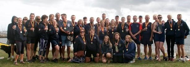 Bridport gig rowing club line up with their medals