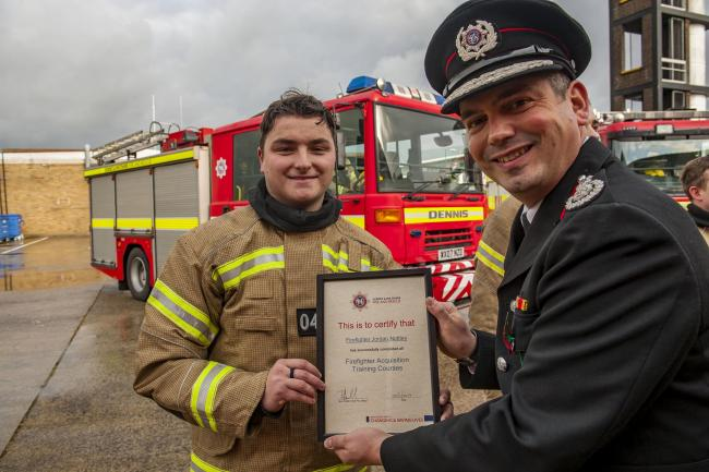 Firefighter Nottley receives a certificate   Picture: Dorset & Wiltshire Fire and Rescue Service