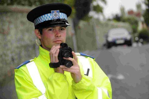 READY AND WAITING: Lyme Regis PCSO Luke White with a speed gun