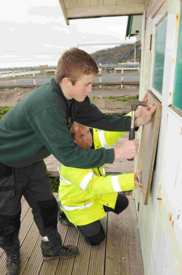 STRIKE: Huts are repaired by council workmen Stephen Hussack, right, and Kyle Knight