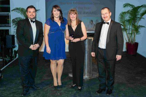 AWARDS SUCCESS: From left, compere Lloyd Griffith, Zoe Jones and manager Lorraine Knowles collecting the award for the tourist information centre, and Neil Quigley