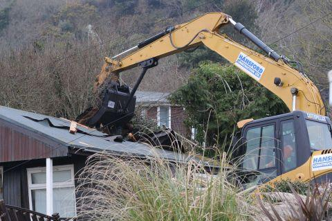 The first chalet being demolished at Ware Cliff in Lyme Regis