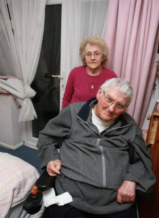 Bridport and Lyme Regis News: Peter and Shirley Williams in their bedroom, which suffered flood damage