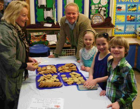 BAKE: Charmouth Primary School pupils Fred Morel, Sophie Broome and Lil Miles selling their biscuits to Pam Turnbull and Andy Morel in aid of the Lyme Regis RNLI