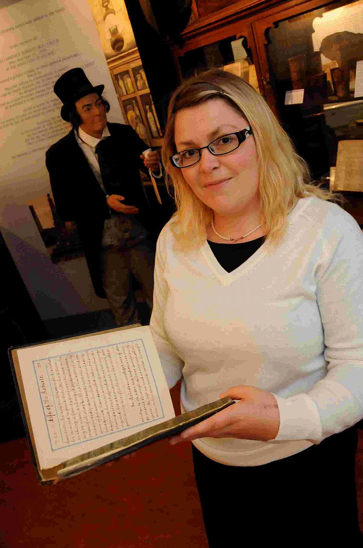 Curator: Emily Hicks with the book on Dr Roberts