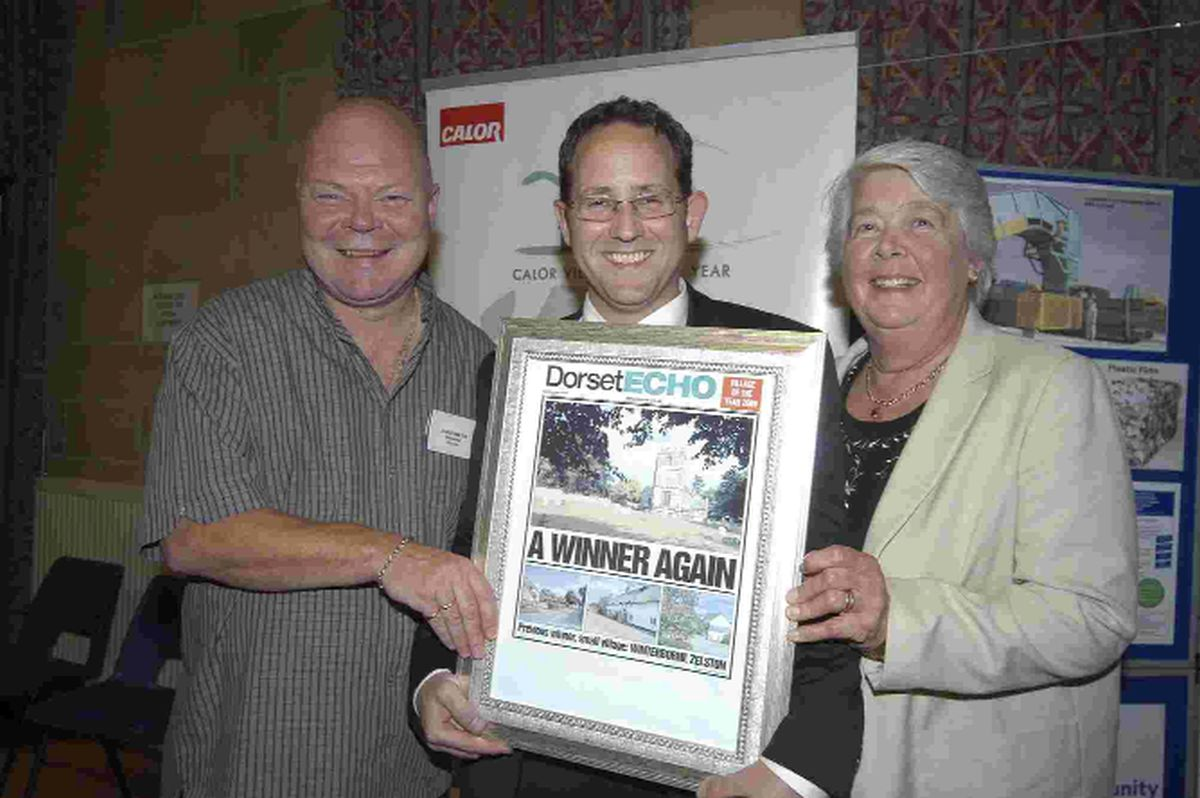 Last year's Dorset Echo award went to Winterbourne Zelston. Former deputy news editor, James Tourgout presents a commemorative front page to  Damen Holden and Rita Burden