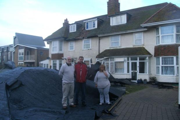 SHOCKED: From left, Bill Vickers, Chas Clarke and Sue Marks in front of the damaged homes in West Bay. There is a car buried under the roofing felt. Picture: Anne Bell