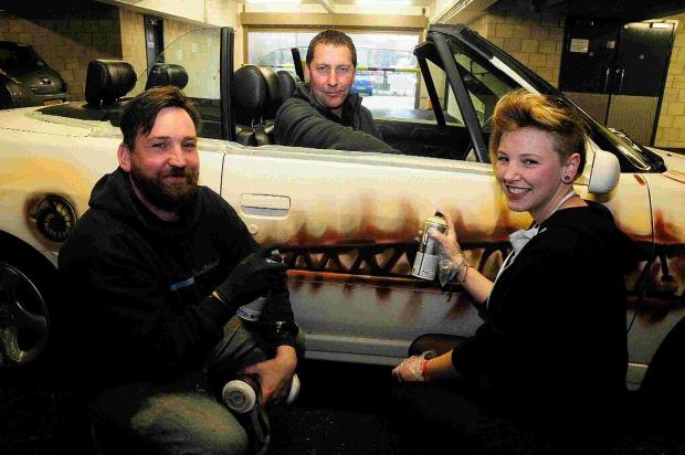 Bridport and Lyme Regis News: Graffiti artists Peter Sheridan and Demi Watts with Monaco or Bust car driver Neil Siford