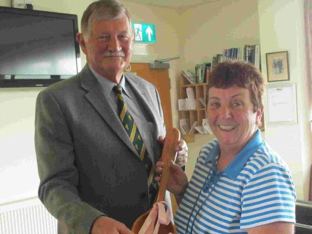 GIFT: Roger Pollock presents Liz Walker with the wooden spoon