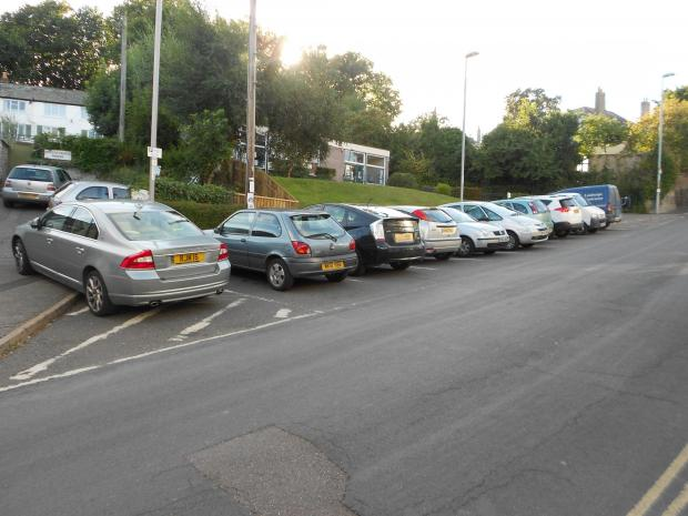 Cars parked outside the library on Silver Street, Lyme Regis