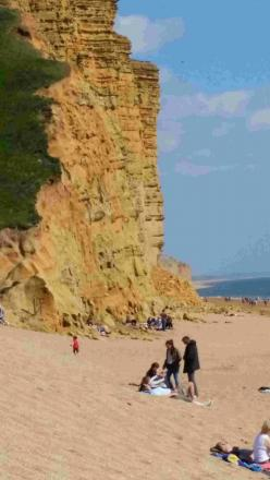 TAKING A RISK: A family is pictured sitting below cliffs near West Bay