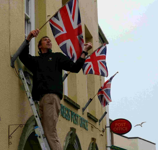 Lyme Regis Town Council operations manager Elliot Herbert puts up the flags