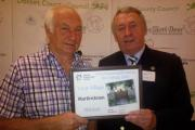 WINNER: David Reed, left, receives the award for Martinstown from Purbeck District Council chairman Cllr Bill Trite