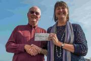 Chris Savory, chairman of the Lyme Regis Society, presents a cheque for £200 to Polly Benfield of the youth music charity B Sharp  Picture: PETER WILES