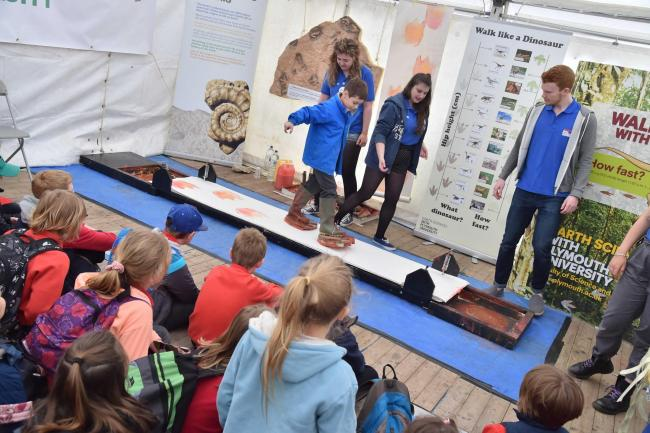 IN THEIR SHOES: Pupils from Parratt and Axe Primary School at the Plymouth University Earth sciences stand, making dinosaur footprints