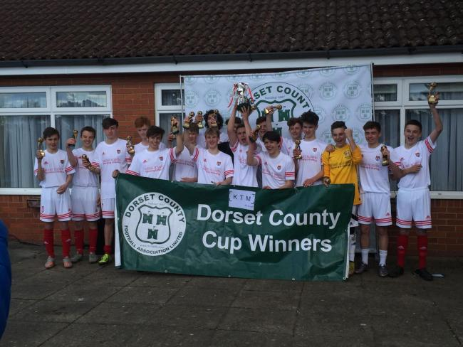 TROPHY TIME: Bridport Youth's under-16s lift the county cup after their win over Dexter Sports