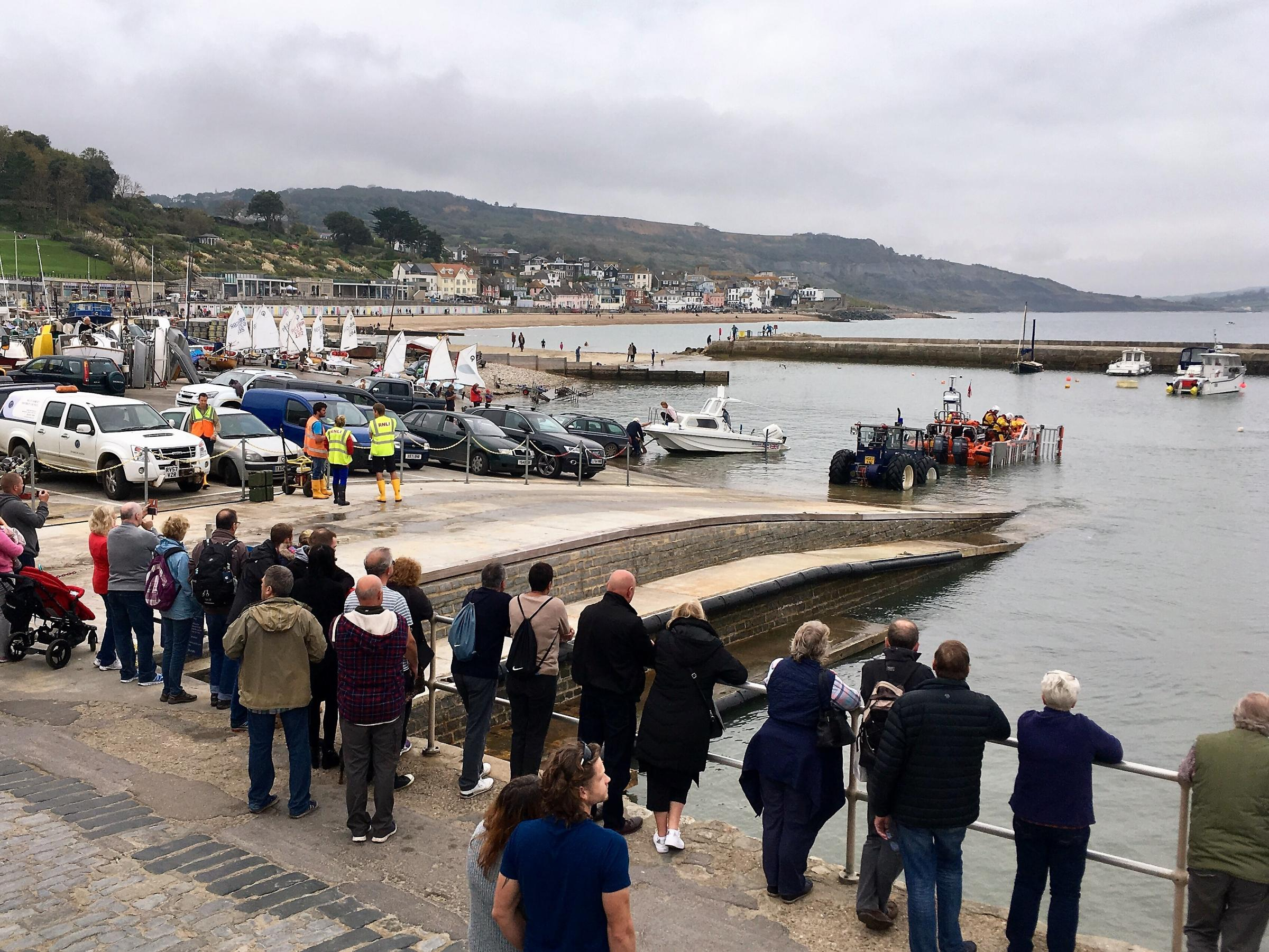 Onlookers at the barbour welcome the return of Lyme Regis lifeboat on Saturday. Photo: Seb Cope