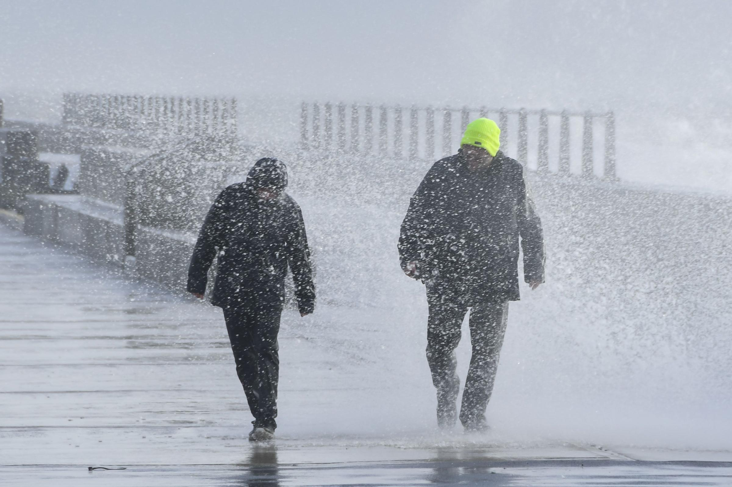 A couple get a soaking on the pier as gale force winds and rough seas from Storm Freya smash against the shoreline at West Bay in Dorset.  3rd March 2019. Picture credit: Graham Hunt Photography...