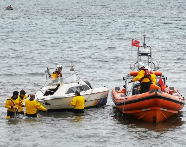 RESCUE: Lyme RNLI lifeboat crew responds to two people in the water and a sinking boat