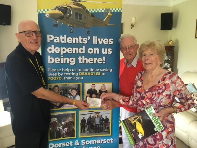 Tony and Margaret Greenham present a cheque for £735 to Alan Harrow, Dorset and Somerset Air Ambulance volunteer